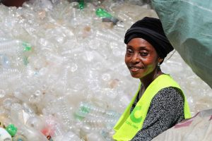 A woman in front a pile of plastic bottles