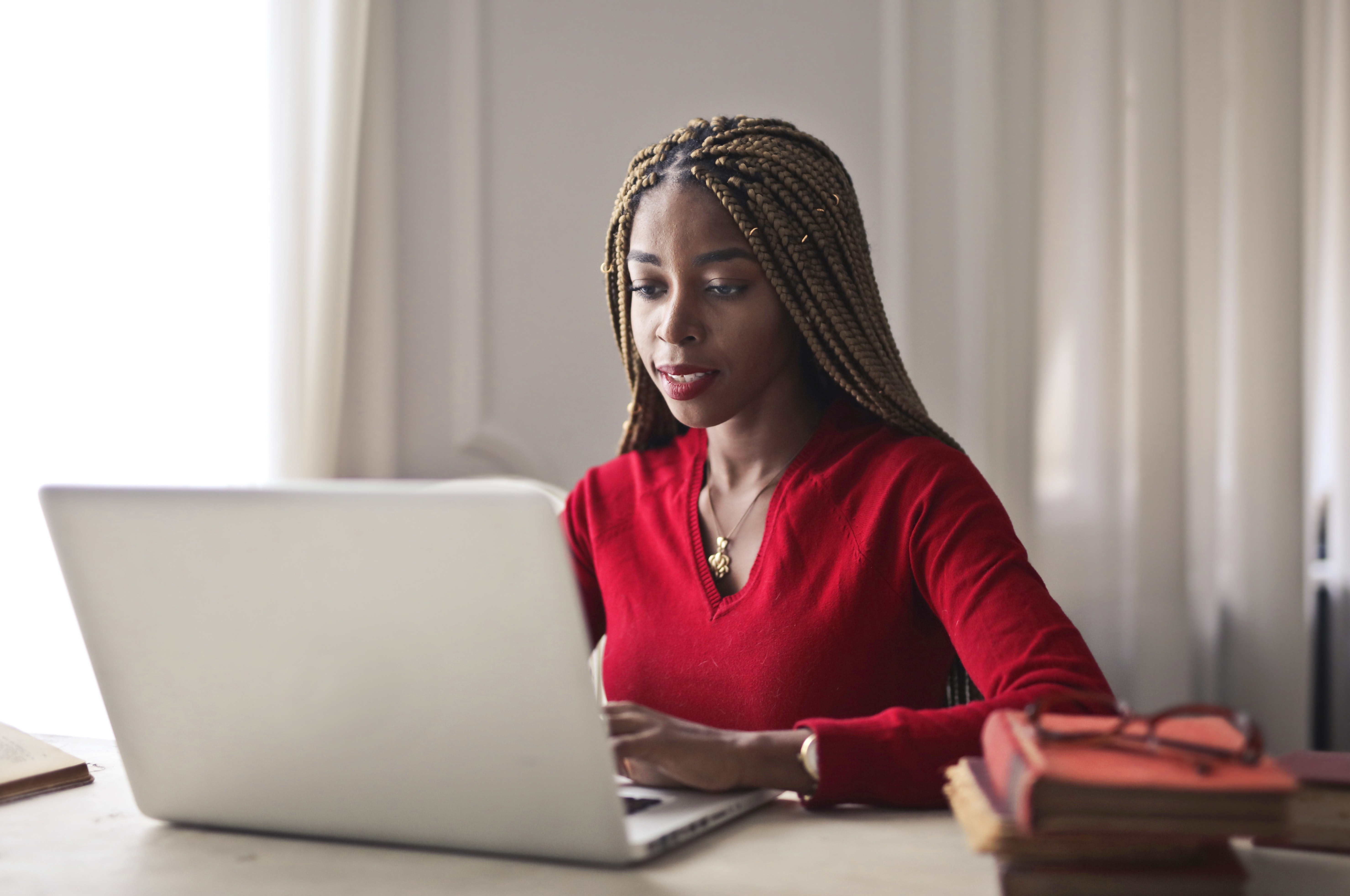 woman in red sweater using laptop, a distance learner